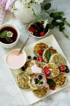 Sommerfrühstückshintergrund hausgemachte hüttenkäsepfannkuchen mit mohnsamen