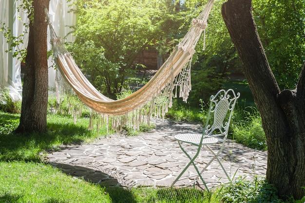 Sommergarten mit hängender hängematte zur entspannung.