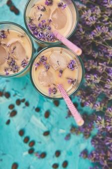 Sommergetränk eiskaffee mit lavendel in glas und kaffeebohnen auf blauem tisch.