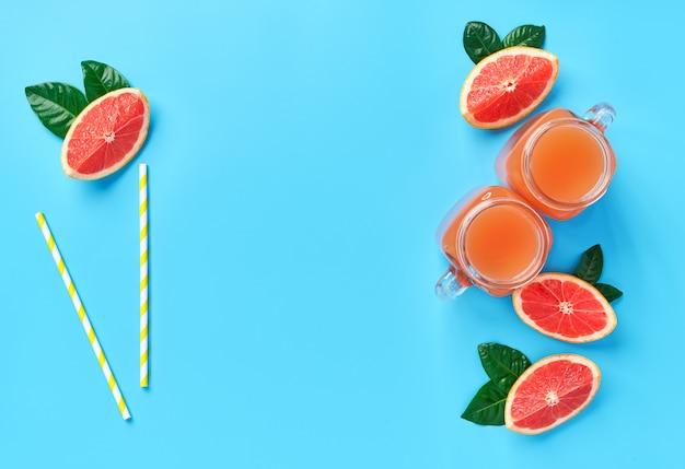Sommergetränk. frischer grapefruitsaft auf einem blauen hintergrund