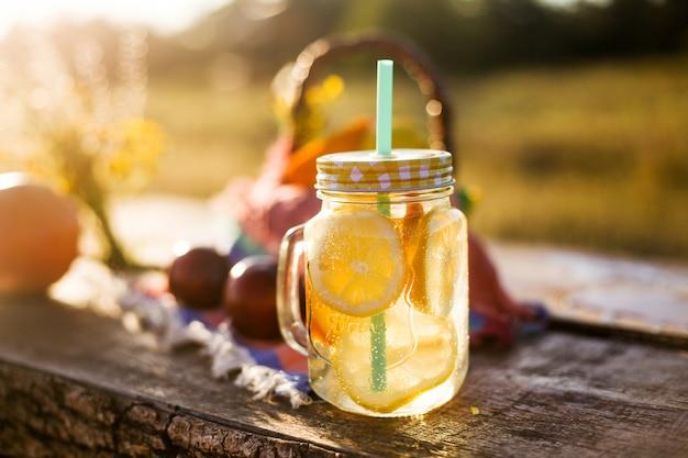 Sommergetränk im glas und korb mit sommer trägt in der sonne, im picknick im freien oder im parteikonzept früchte