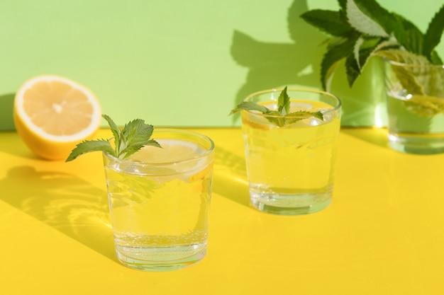 Sommergetränk. kühles erfrischungsgetränk mit minze und zitrone im glas. minimalismus. natürliche frische limonade mit harten schatten auf gelbem hintergrund