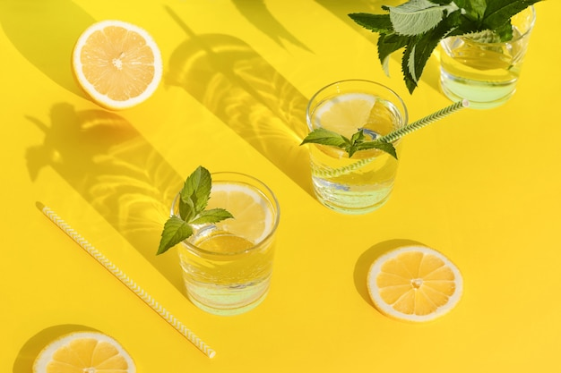 Sommergetränk. kühles erfrischungsgetränk mit minze und zitrone im glas. null abfall nach hause. minimalismus. frische limonade mit harten schatten auf gelbem hintergrund