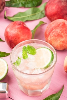 Sommergetränk mit kaltem alkohol, bellini-cocktail mit pfirsichglasur und minzblättern,