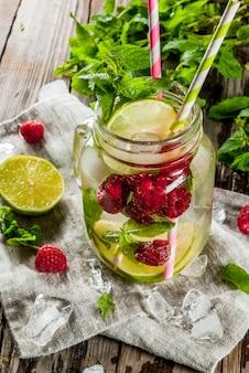 Sommergetränke, cocktails. veganes essen. entgiftungswasser mit limette, minze und frischen bio-himbeeren