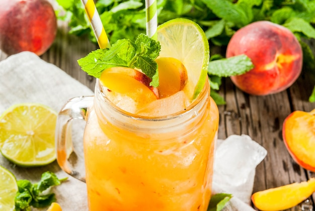 Sommergetränke, cocktails. veganes essen. pfirsich-smoothies, saft oder limonade. in einem einmachglas mit limette, gehacktem eis und minzblättern. auf einem alten rustikalen holztisch mit bestandteilen.