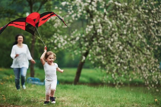 Sommerglück. positives weibliches kind und großmutter, die mit rotem und schwarzem drachen in den händen draußen laufen