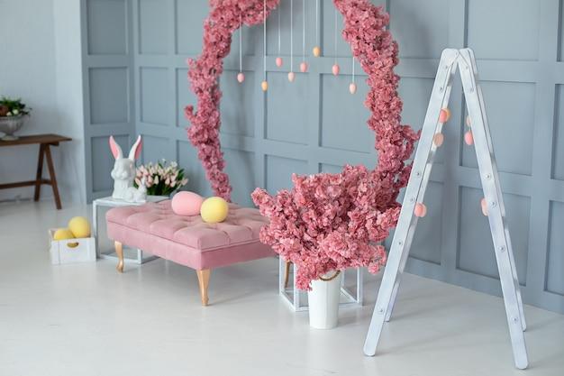 Sommerhausinnenraum mit rosa sofablüte großer sakura-kranz an der wand-osterdekoration des wohnzimmers