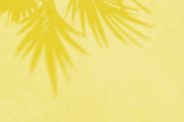 Sommerhintergrund der schattenzweigblätter an einer wand. beleuchtende pantone-farbe des jahres 2021.