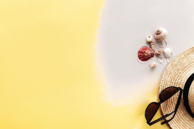 Sommerhintergrund konzeptionelle wohnung mit sand, muscheln, strohhut und sonnenbrille auf gelbem hintergrund. foto in hoher qualität