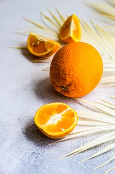 Sommerhintergrund mit scheiben von organischen frischen reifen orangefarbenen früchten auf betonoberfläche