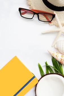 Sommerhintergrund mit starfish, oberteilen, kokosnuss, gelbem notizbuch, hut und brillen auf weißem hintergrund, draufsicht