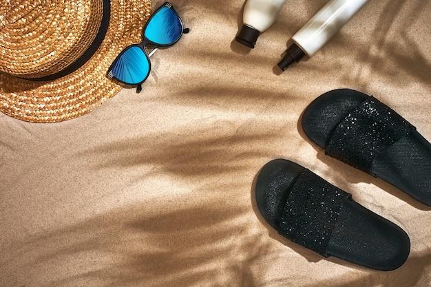 Sommerhintergrund mit strohhut-sonnenbrille-sonnenschutzflasche und flip-flops