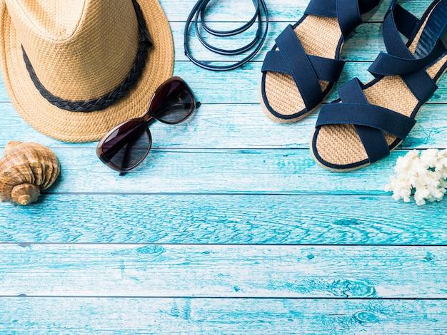 Sommerhintergrund strohhut armbänder sandalen sonnenbrillen muscheln auf einer blauen tabelle