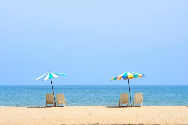 Sommerhintergrund, stuhl und bunter regenschirm auf strand- und seehintergrund