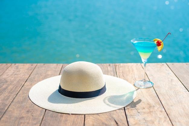 Sommerhintergrund, weißer hut und sommer trinkend auf strand