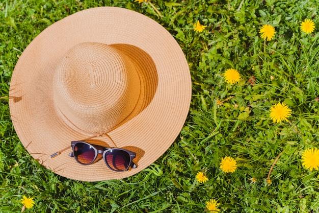 Sommerhut auf dem gras mit sonnenbrille