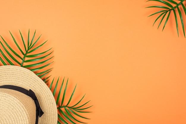 Sommerhut lag auf grünem blatt auf orange hintergrund. speicherplatz kopieren.
