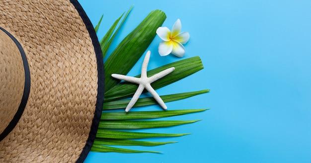 Sommerhut mit seestern und plumeria oder frangipani-blume auf tropischen palmblättern auf blauem hintergrund. sommerferienkonzept genießen.