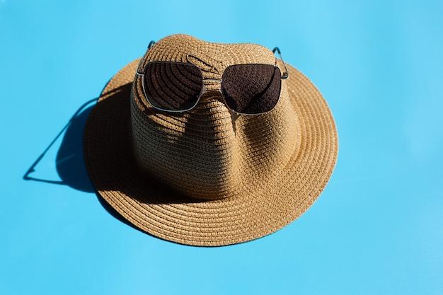 Sommerhut mit sonnenbrille auf blauem hintergrund. urlaubskonzept genießen.