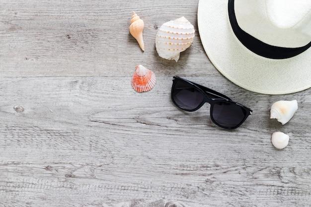 Sommerhut und sonnenbrille auf holztisch