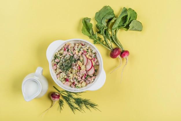 Sommerjoghurt kalte suppe mit ei, gurke, wurst und dill in einem teller