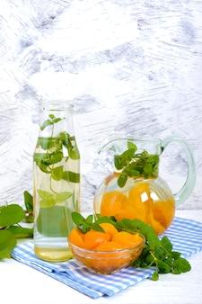 Sommerkalte getränke. köstliches erfrischendes getränk mit aprikose und minze in gläsern auf einem weißen hölzernen hintergrund. kompott aus früchten.