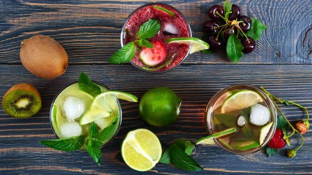 Sommerkalte getränke mit frischem obst, beeren und minze. erdbeermojito, kirsch-smoothies, kiwi-cocktail in gläsern auf einem holztisch