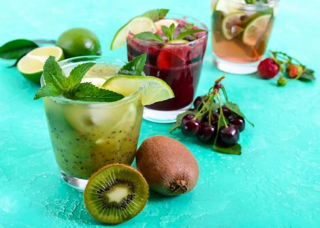 Sommerkalte getränke mit frischem obst, beeren und minze. erdbeermojito, kirschsmoothies, kiwi-cocktail in gläsern.