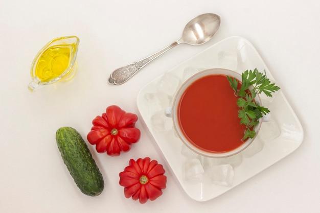 Sommerkalte tomatensuppe. eis auf einem teller. satz von produkten für gazpacho, weißer hintergrund
