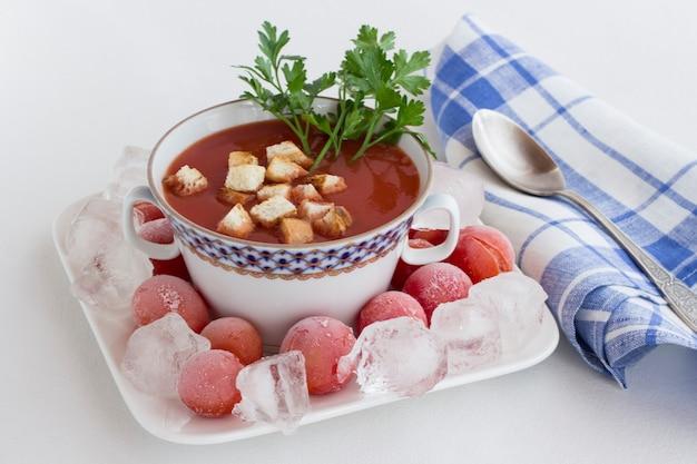 Sommerkalte tomatensuppe (gazpacho). eis und gefrorene tomaten auf einem teller. blaue karierte serviette, weißer hintergrund