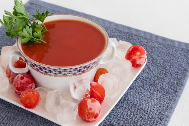 Sommerkalte tomatensuppe (gazpacho). eis und gefrorene tomaten auf einem teller. graue serviette, weiße oberfläche