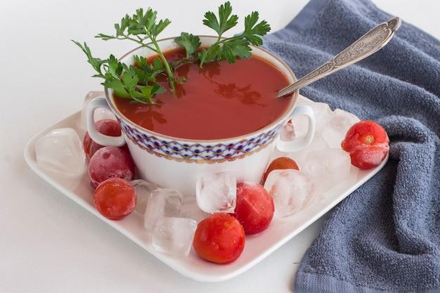 Sommerkalte tomatensuppe (gazpacho). eis und gefrorene tomaten auf einem teller. graue serviette, weißer hintergrund