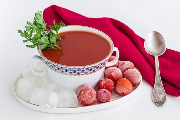 Sommerkalte tomatensuppe (gazpacho). eis und gefrorene tomaten auf einem teller. rote serviette, weißer hintergrund