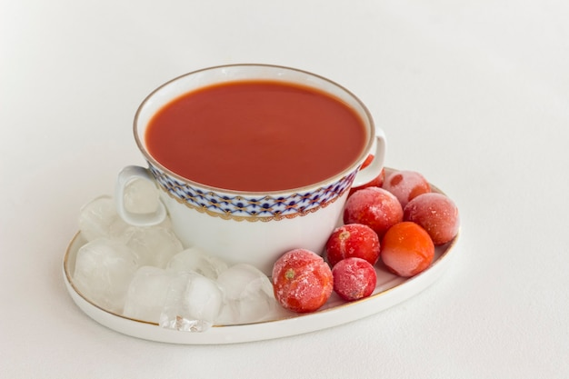 Sommerkalte tomatensuppe (gazpacho). eis und gefrorene tomaten auf einem teller, weiße oberfläche