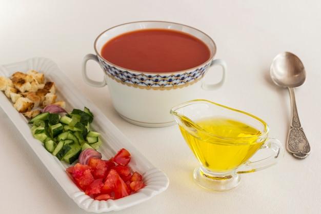 Sommerkalte tomatensuppe. produktsatz für gazpacho, weiße oberfläche