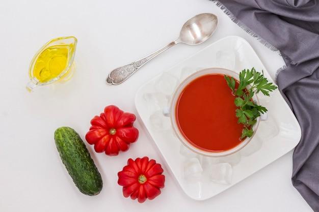 Sommerkalte tomatensuppe. satz von produkten für gazpacho, eis auf einem teller. graue serviette, weißer hintergrund