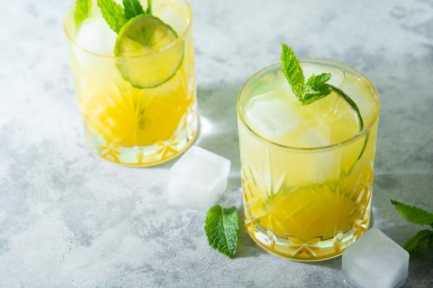 Sommerkaltgetränk mit eiswürfeln, saft und limettenfrucht, sommerliche erfrischungsgetränke. zitrus köstlicher saft.