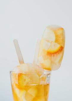 Sommerkaltgetränke zitrusfruchtcocktail orange und zitrone mit eis und eis am stiel