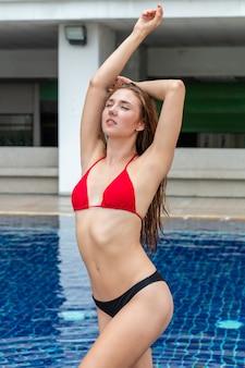 Sommerkaukasisches mädchenmodell im bikini stehend und posierend nahe dem pool.