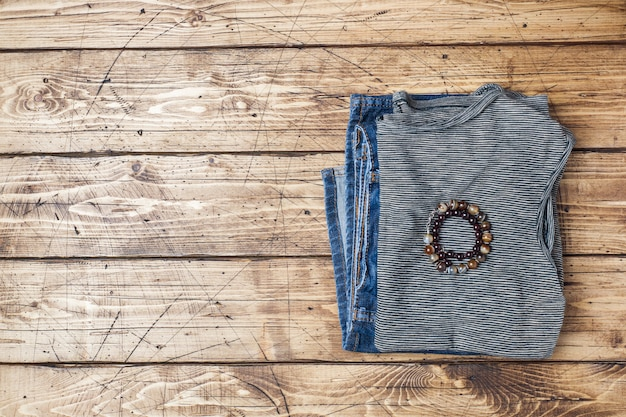 Sommerkleidung für frauen. flaches laienmode-foto. graues gestreiftes t-shirt und blue jeans auf hölzernem hintergrund.