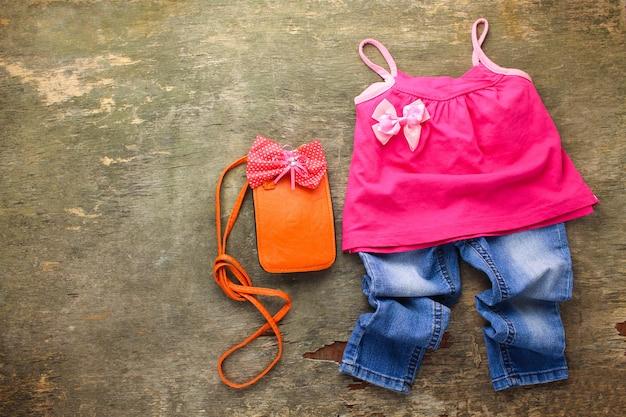 Sommerkleidung für kinder: t-shirt, jeans, handtasche. ansicht von oben.