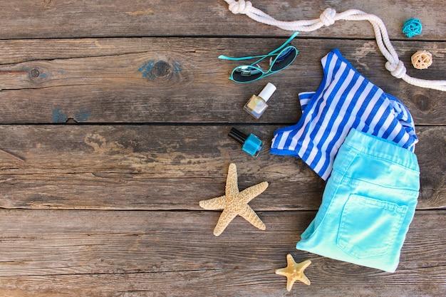 Sommerkleidung und -zubehör der frauen auf altem hölzernem hintergrund. draufsicht, flach zu legen.
