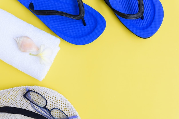 Sommerkollektion, flach gelegte muschel, blaue flipflops, hut, weißes handtuch und frangipani-blume auf gelbem hintergrund