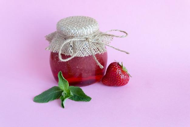 Sommerkonservierung von marmelade. erdbeermarmelade mit minze, erdbeerbeeren auf einem rosa hintergrund.