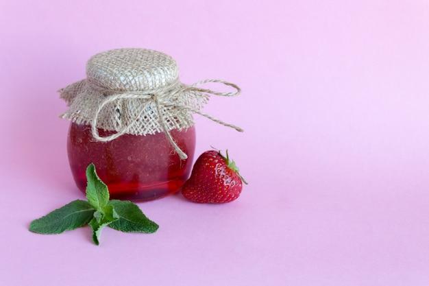 Sommerkonservierung von marmelade. erdbeermarmelade mit minze, erdbeerbeeren auf einem rosa. kopieren