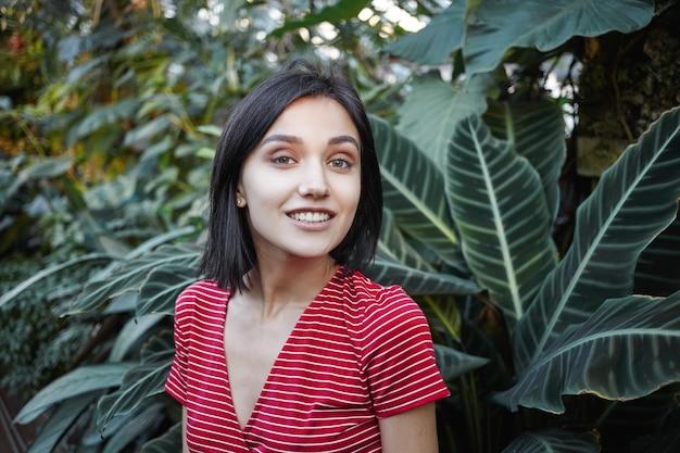 Sommerkonzept. bild der glücklichen schönen jungen bobhaarigen dame mit breitem charmantem lächeln, das ruhe im freien hat, im wald oder im park spazierend, zwischen grünen exotischen pflanzen stehend und grinsend steht