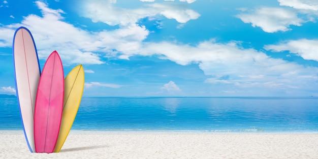 Sommerkonzept-flyer. surfbretter mit strand, sand und meer oder meer im hintergrund. blaues wasser und himmel mit wolken. urlaub, sommer, erholungsort. exemplar für werbung. kunst-collage.