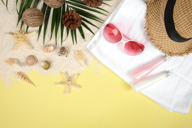Sommerkonzept und -zubehör (oberteile, starfish, kokosnussblatt) mit sandigem strand