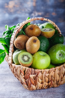 Sommerkorb mit grünem obst und gemüse.